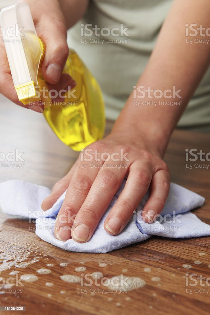 Woman Using Spray To Clean Wooden Surface royalty-free stock photo