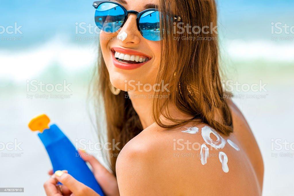 Woman using sun cream on the beach stock photo