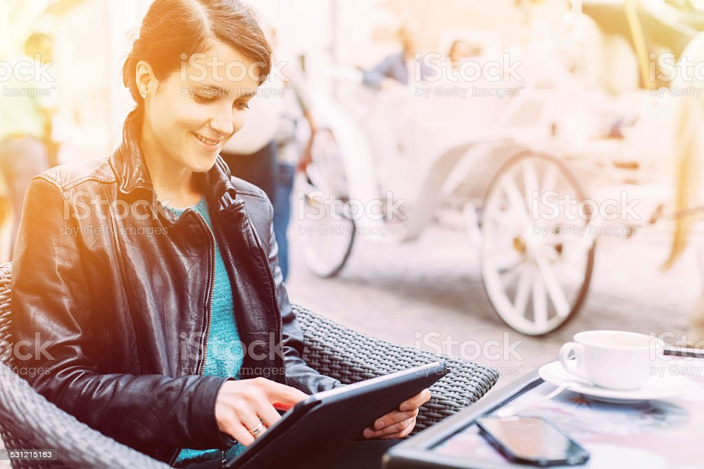 Woman using tablet at cafe stock photo
