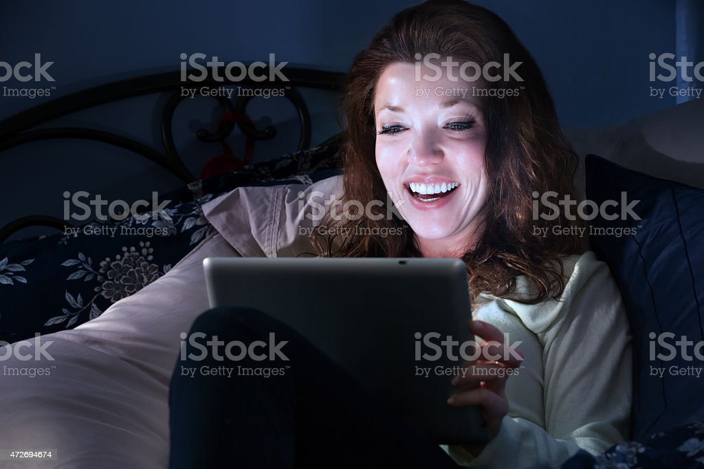 woman using tablet computer in bed at night stock photo