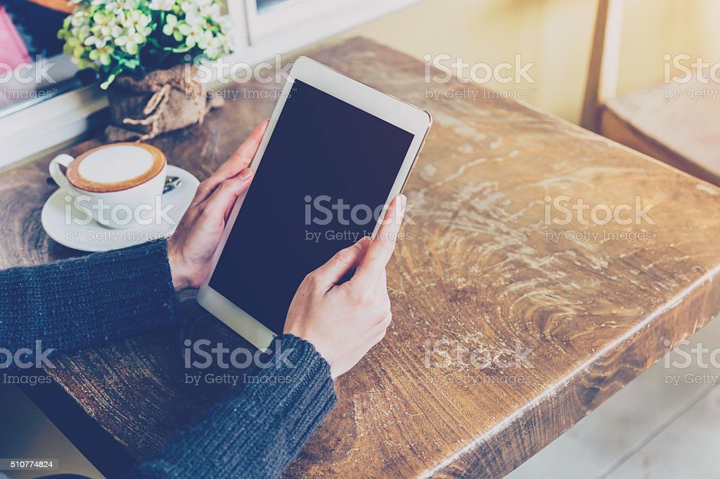 Woman using tablet in coffee shop with vintage tone. stock photo