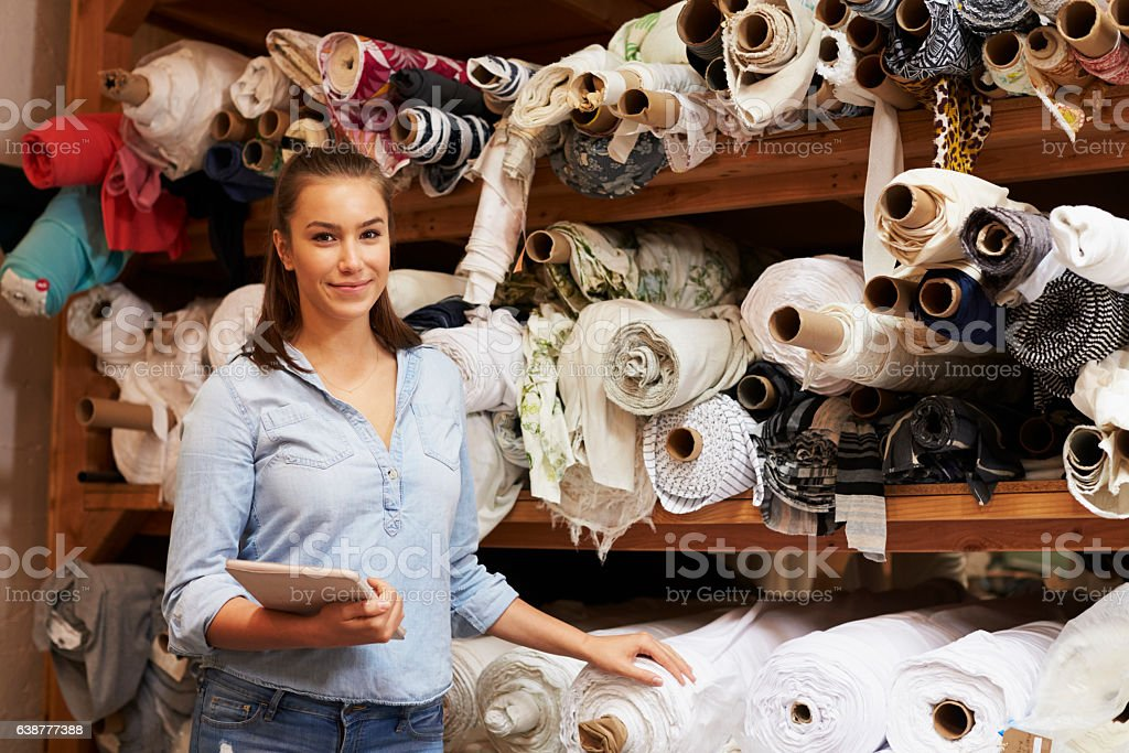 Woman using tablet in fabric storage warehouse, portrait stock photo