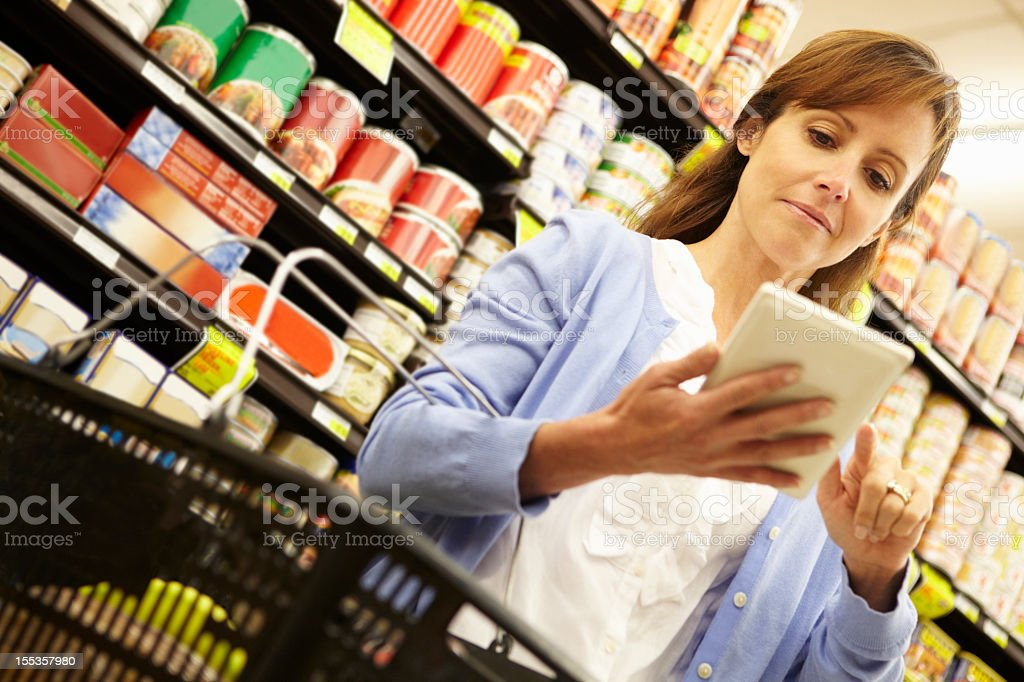 Woman using tablet in grocery store stock photo