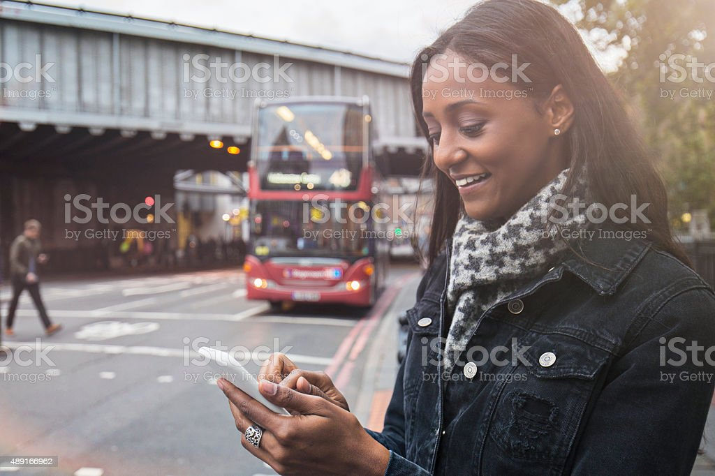 Woman using the new technologies for a taxi in London stock photo