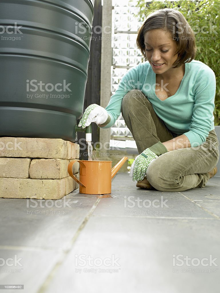Woman using the recycled water. stock photo