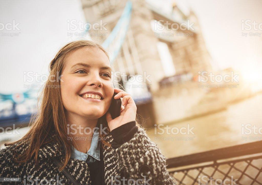 woman using the smartphone under tower bridge royalty-free stock photo