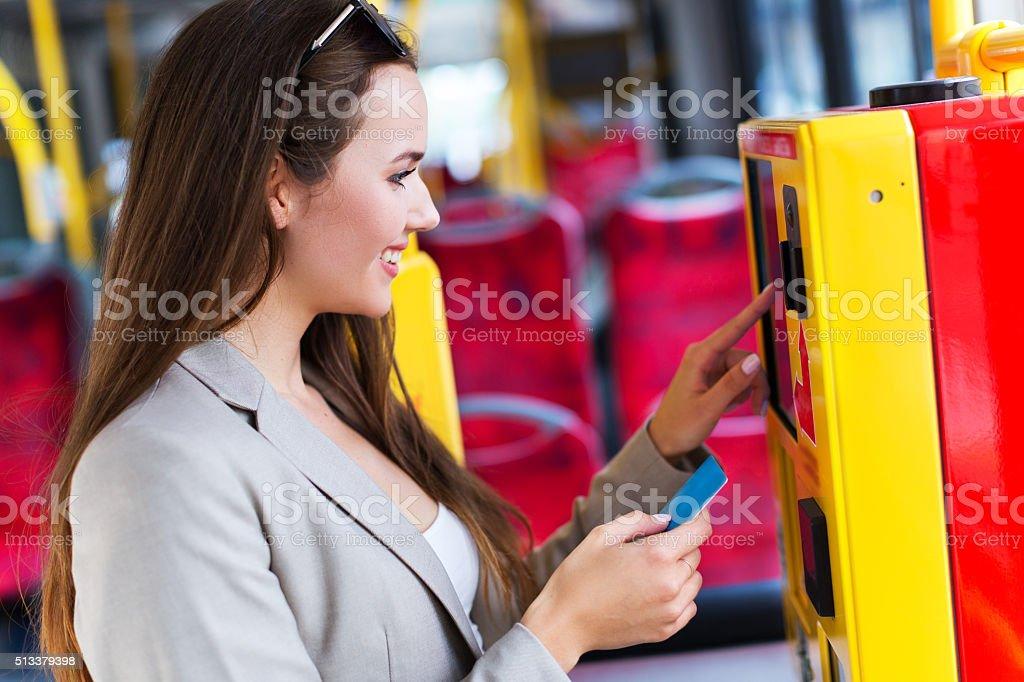 Woman using ticket machine on bus stock photo