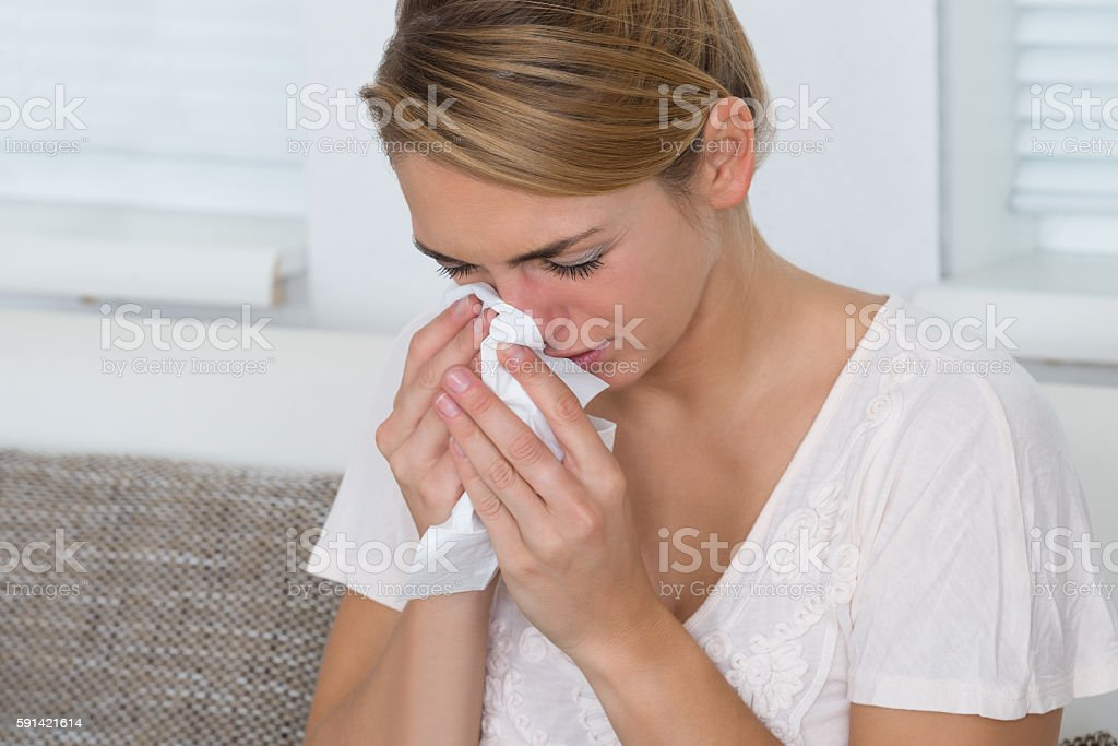 Woman Using Tissue While Suffering From Cold stock photo