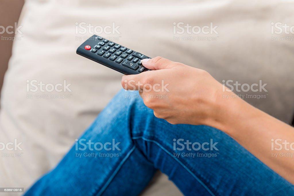 Woman using TV Remote Control stock photo