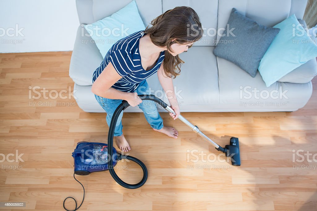 Woman using vacuum cleaner on wooden floor stock photo