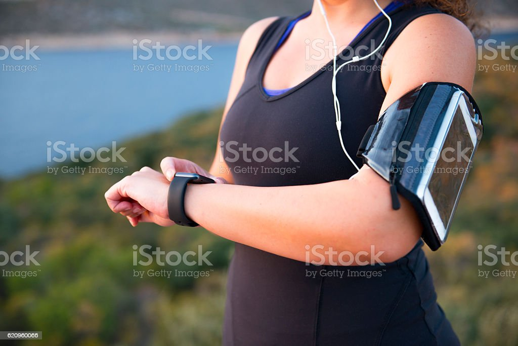 Woman using wearable technology while execising stock photo