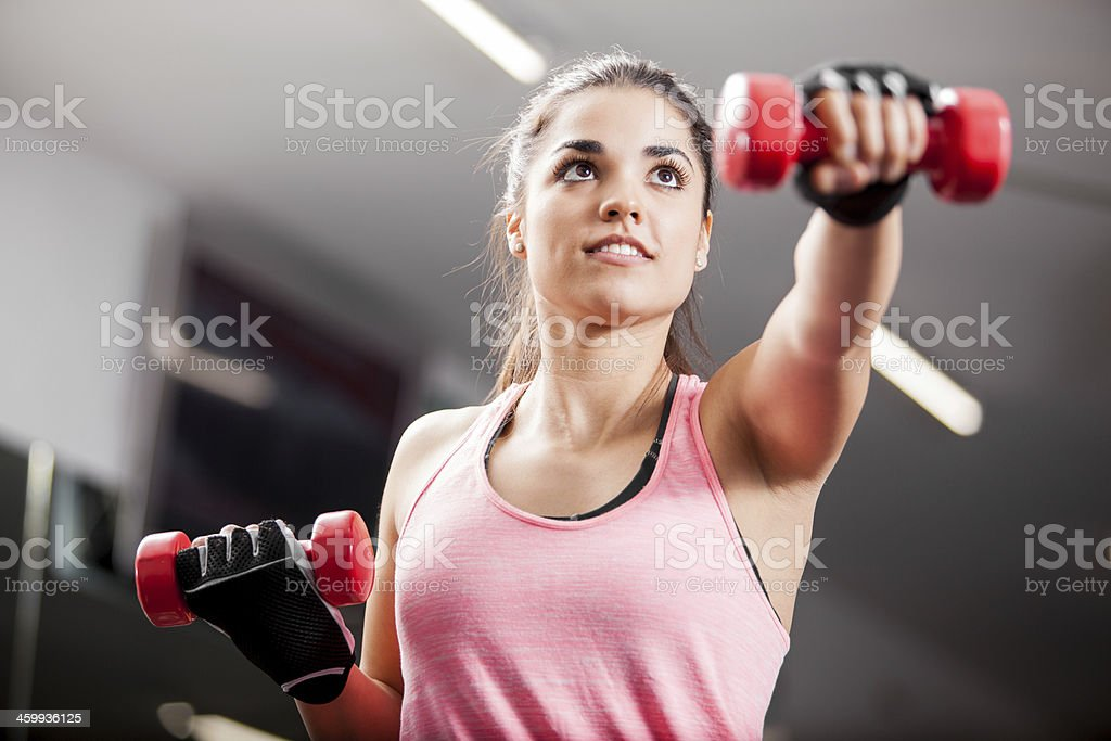 Woman using weights at the gym stock photo