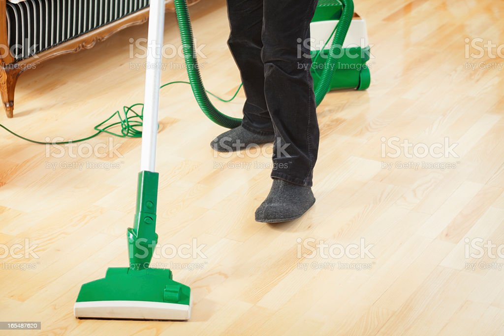 Woman vacuum cleaning wooden floor royalty-free stock photo