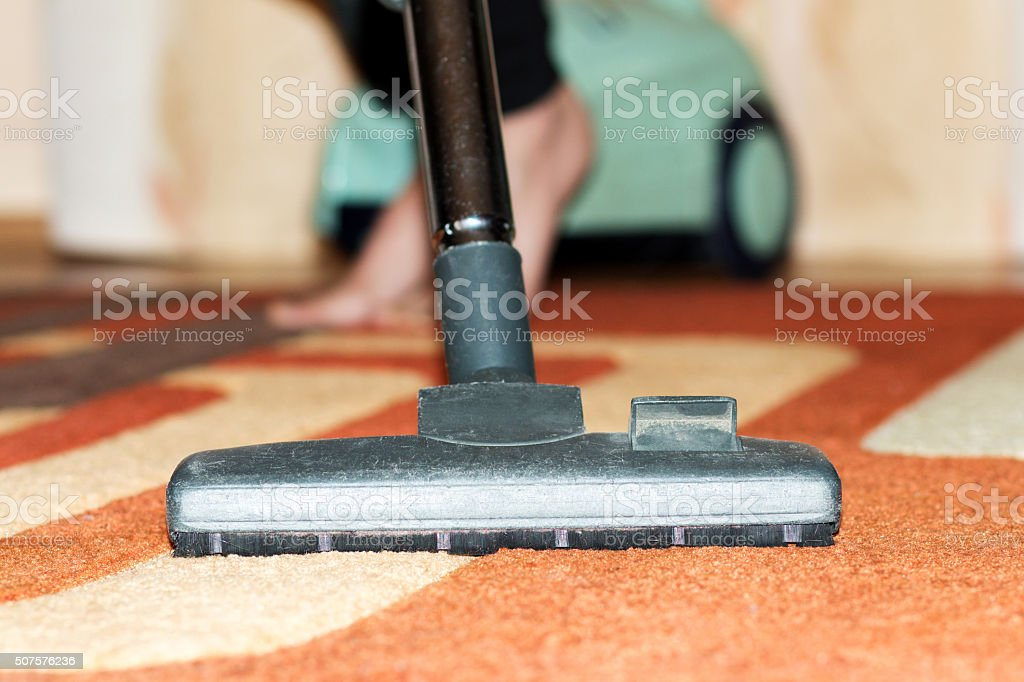 woman vacuuming carpet in living room stock photo
