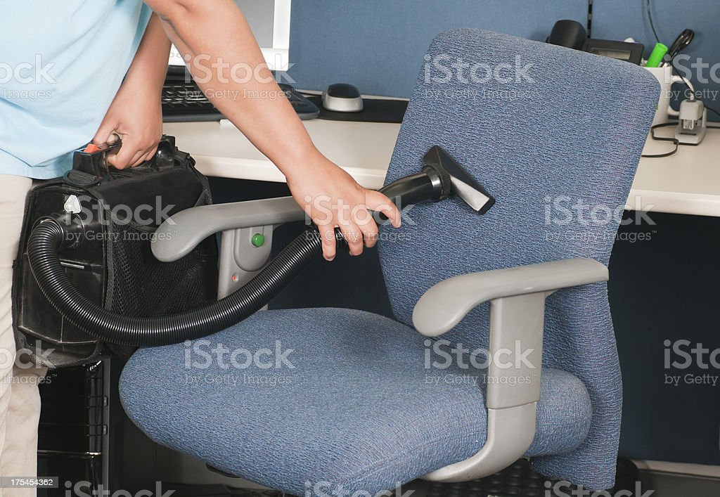 Woman Vacuuming Chair Upholstery royalty-free stock photo