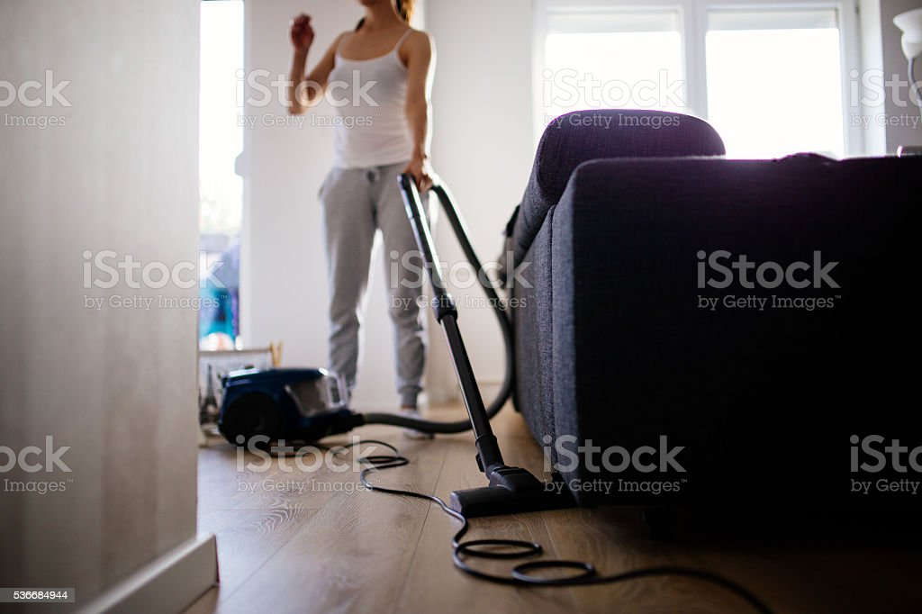 Woman vacuuming living room stock photo
