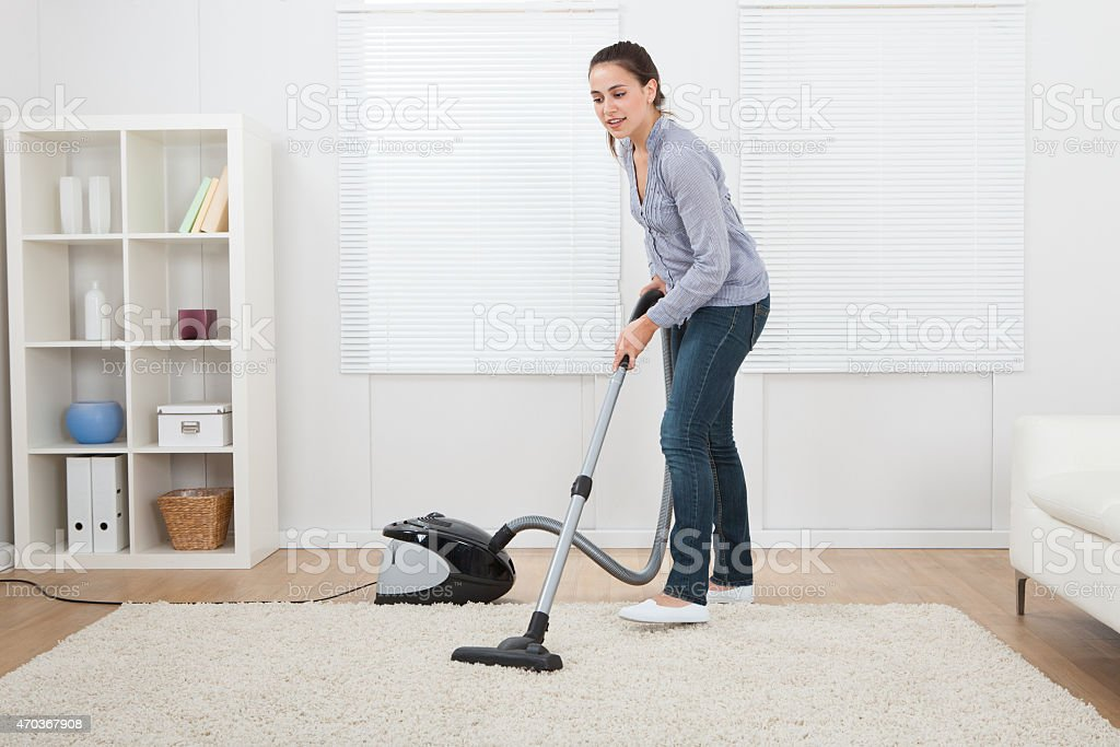 Woman Vacuuming Rug At Home stock photo