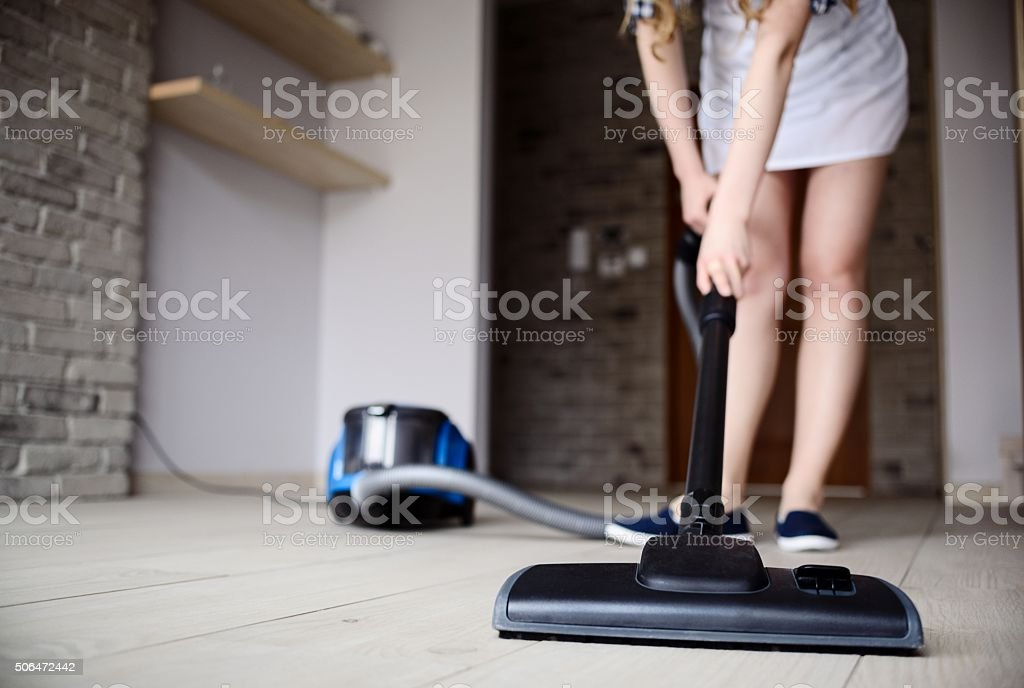 Woman vacuuming the floor. stock photo