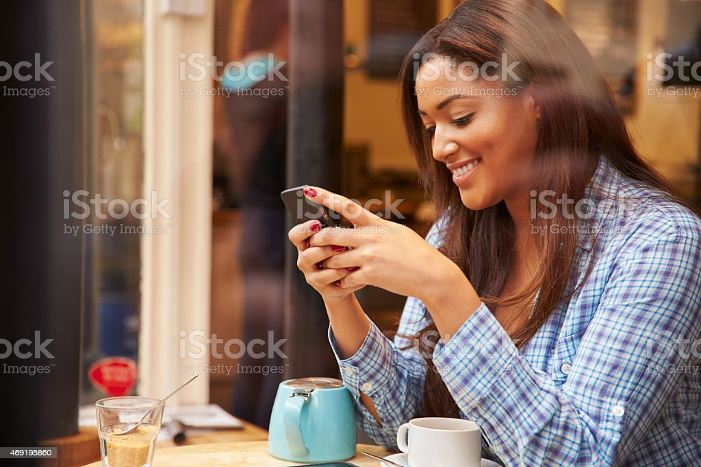 Woman Viewed Through Window Of Caf' Using Mobile Phone stock photo