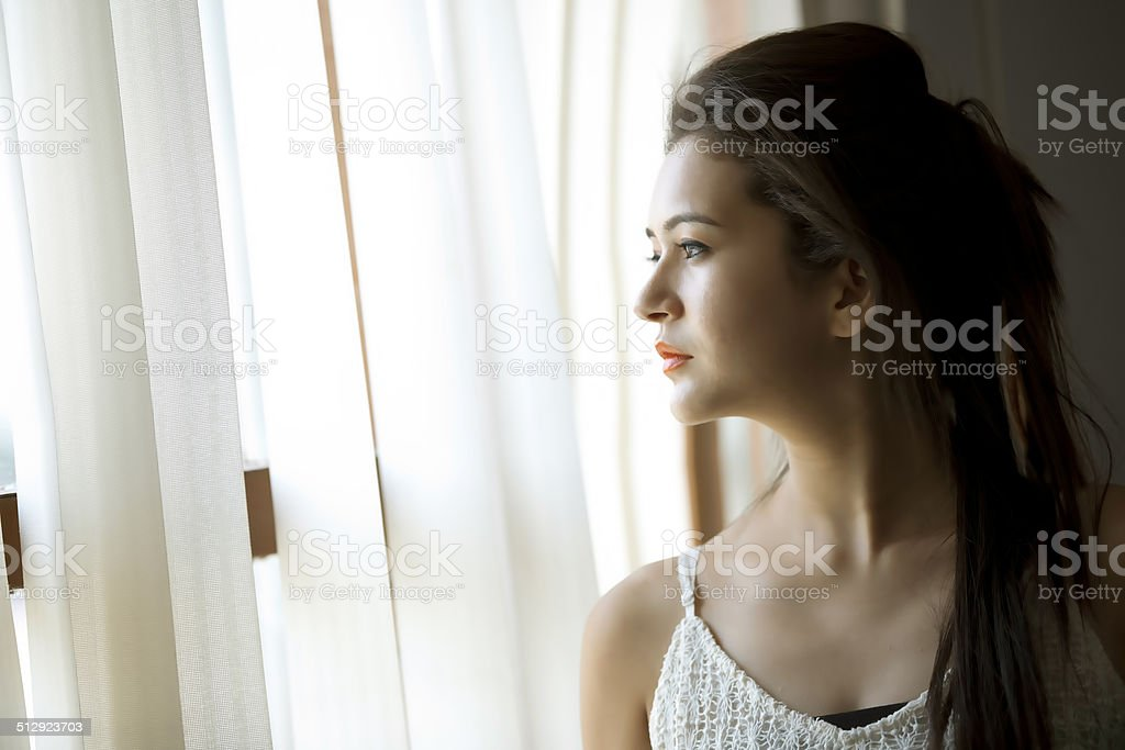 Woman viewed through window stock photo