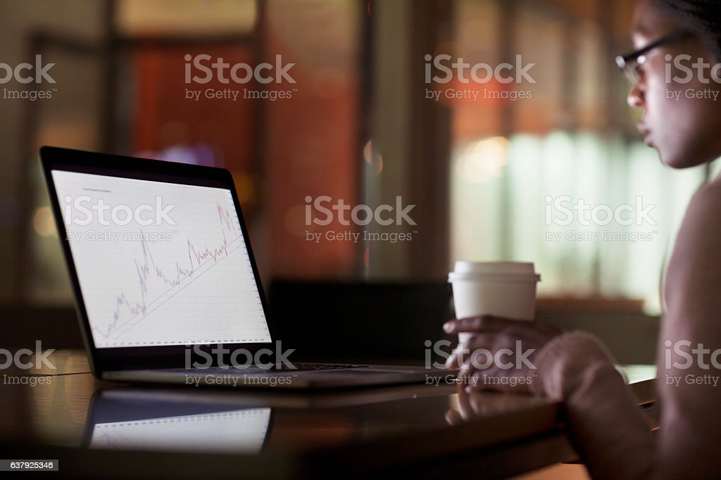 Woman viewing laptop screen with graph diagram stock photo