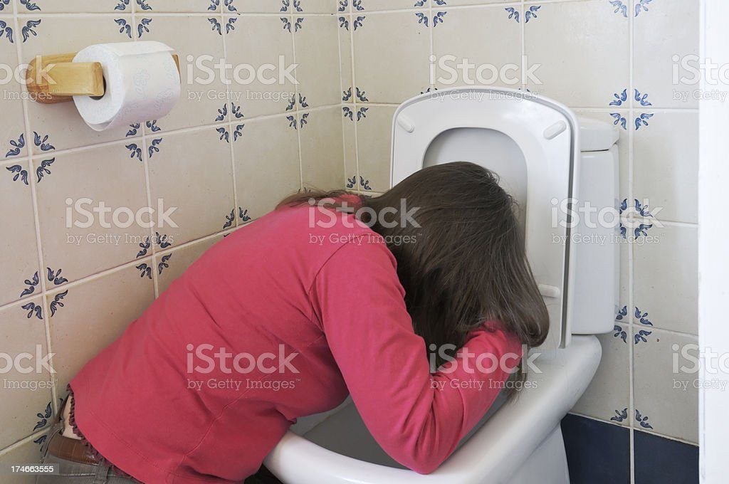 woman vomiting in toilet stock photo