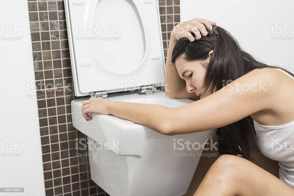 Woman vomiting into the toilet bowl stock photo