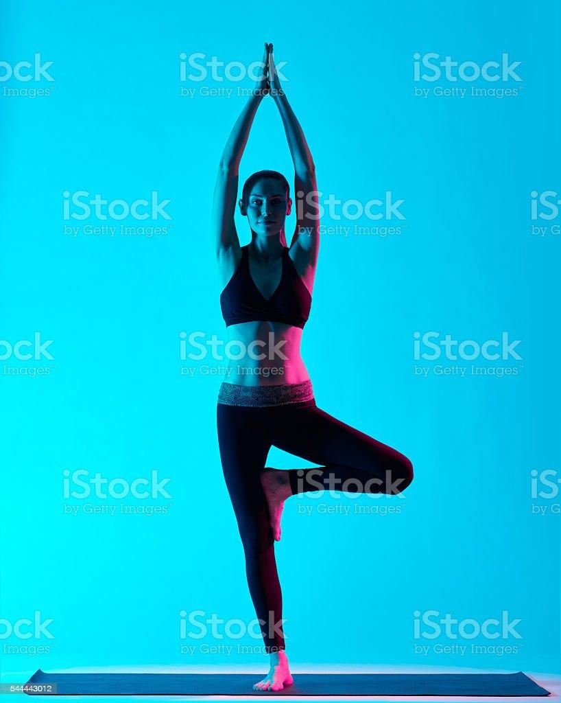 woman Vriksasana yoga exercices tree pose stock photo