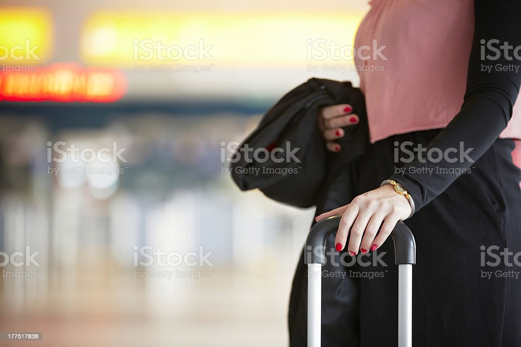 A woman waiting at the airport with her luggage stock photo
