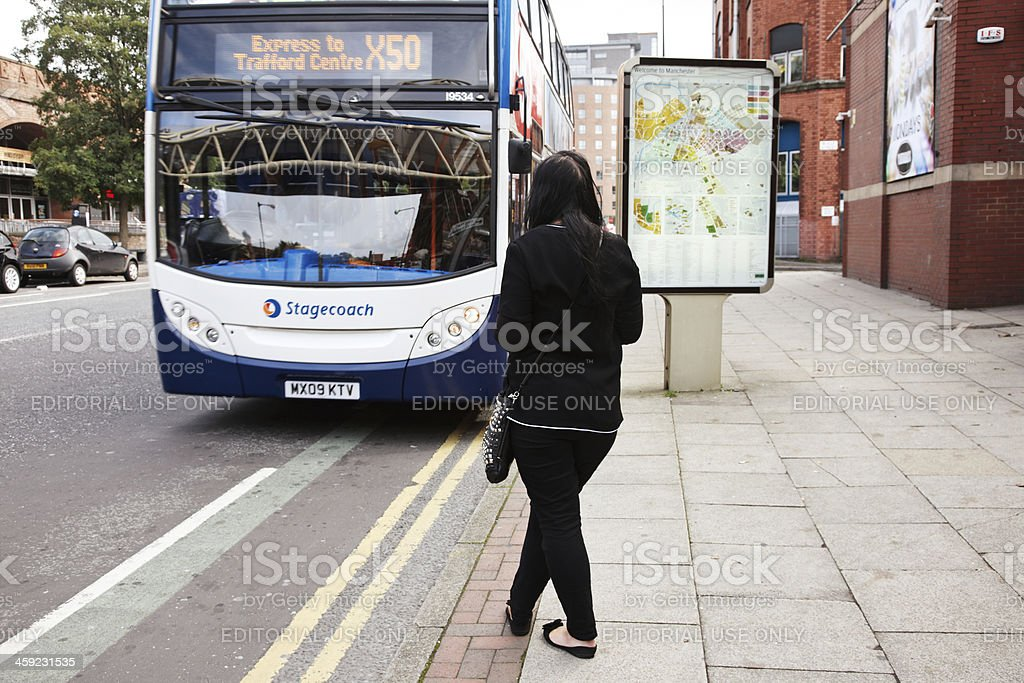 Woman waiting for a bus to stop stock photo