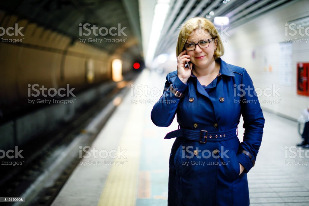 Woman waiting for a train at the metro platform stock photo