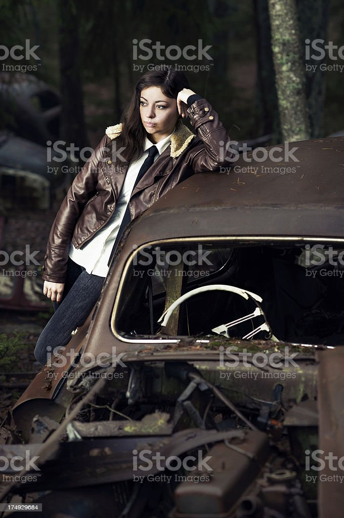 Woman waiting in front of a rusty and destroyed car royalty-free stock photo
