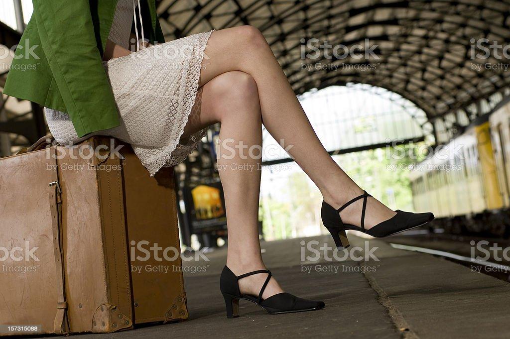 woman waiting on railroad station platform stock photo