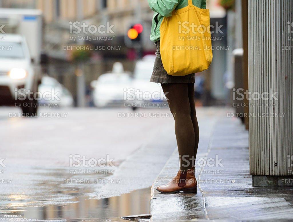 Woman waiting to cross rain wet street stock photo