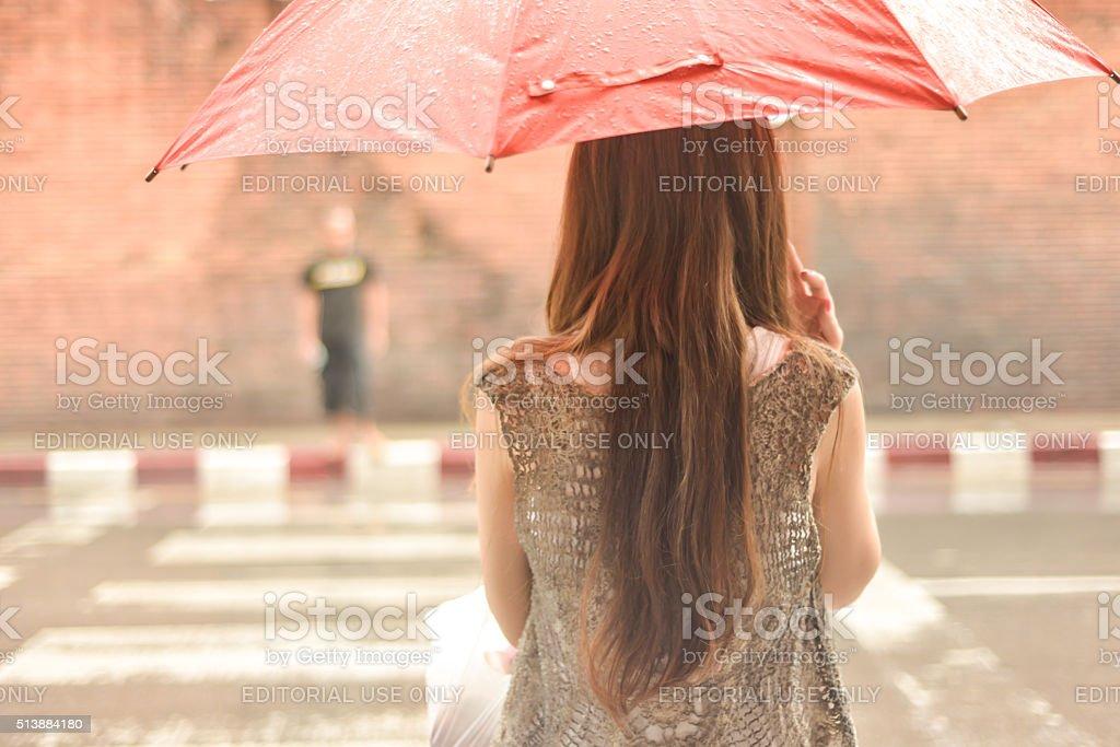 Woman Waiting to Cross Street in Rain with Umbrella stock photo