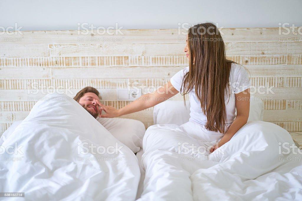 woman waking husband stock photo
