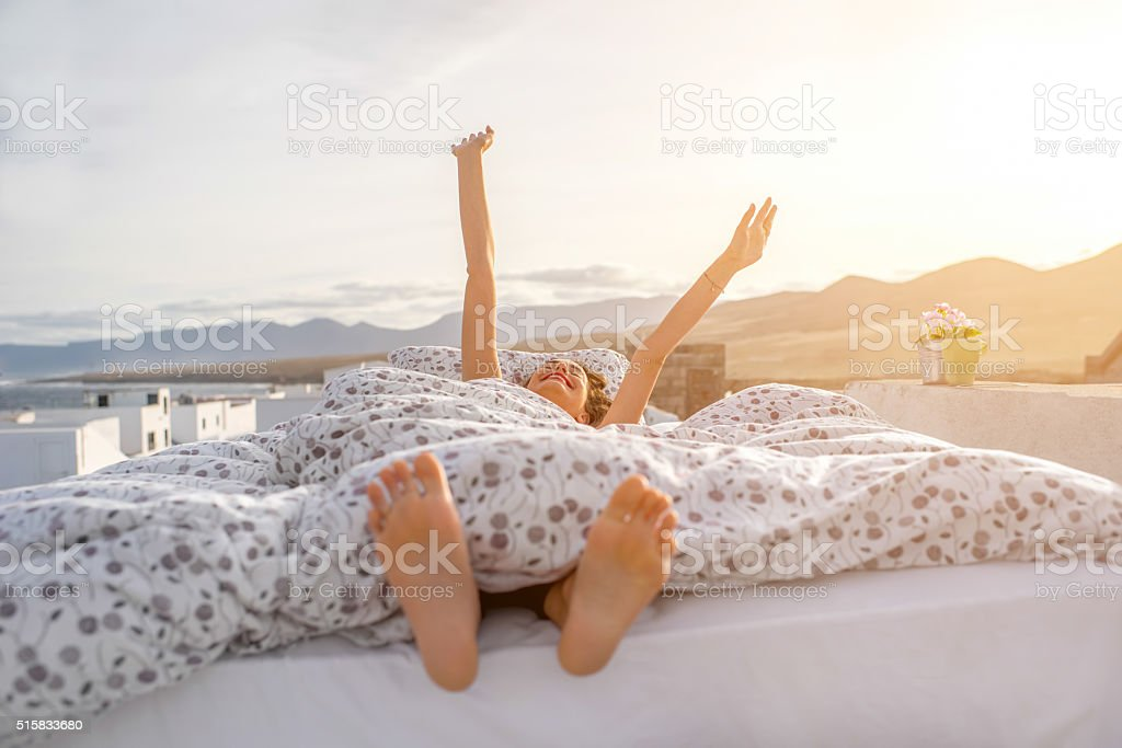 Woman waking up outdoors on the rooftop stock photo