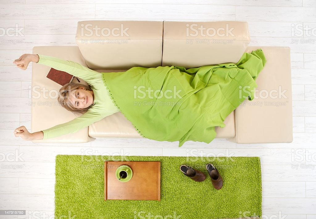 Woman waking up stretching on couch royalty-free stock photo