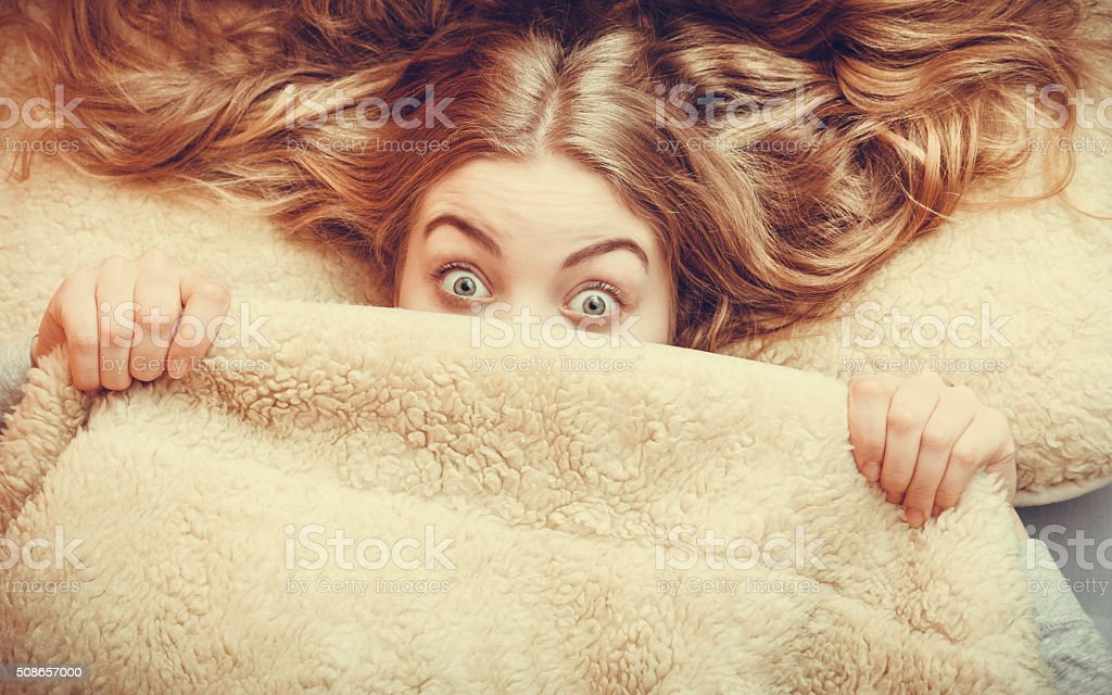 Woman waking up under wool woolen blanket. stock photo