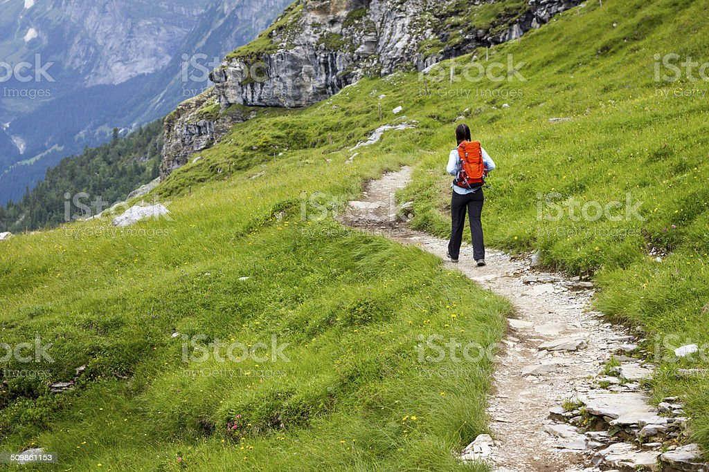 Woman Waling on Winding Mountain Path stock photo