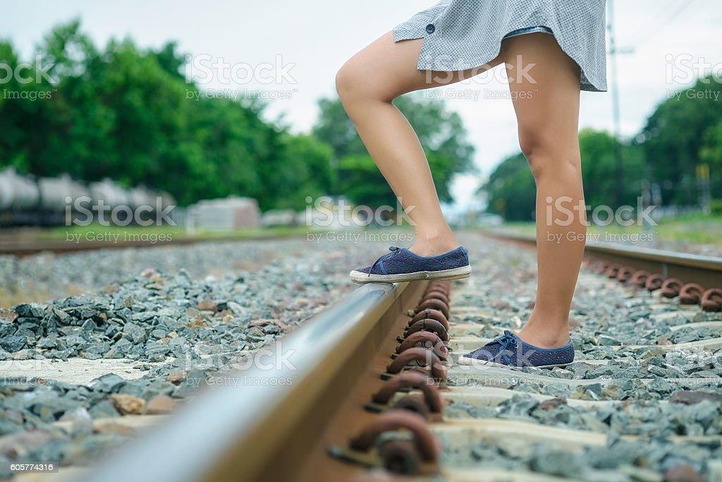 Woman walking across the railway stock photo