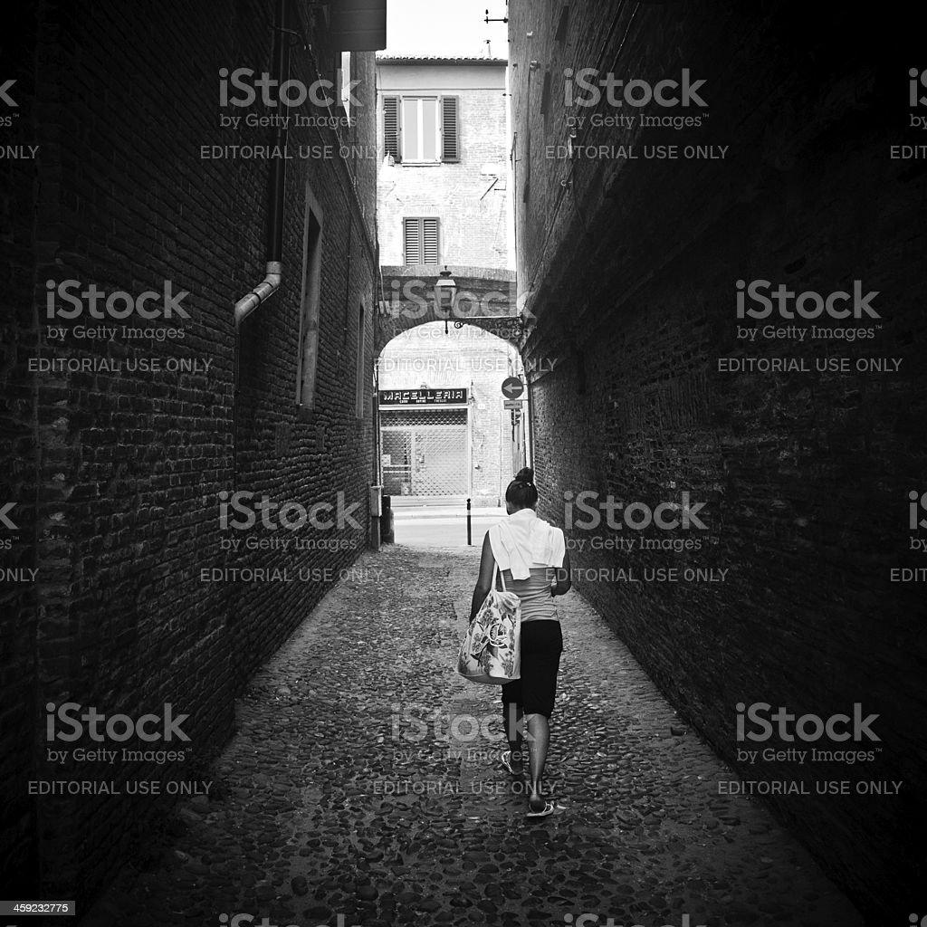 Woman walking alone in a dark alley stock photo