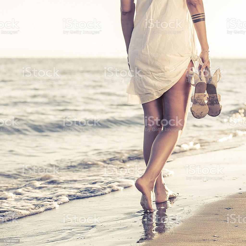 Woman walking alone on the beach royalty-free stock photo