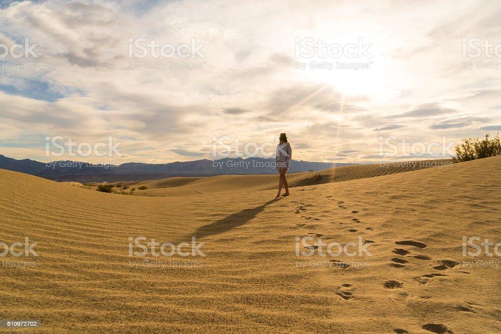 Woman walking along Desert Sand Dunes stock photo