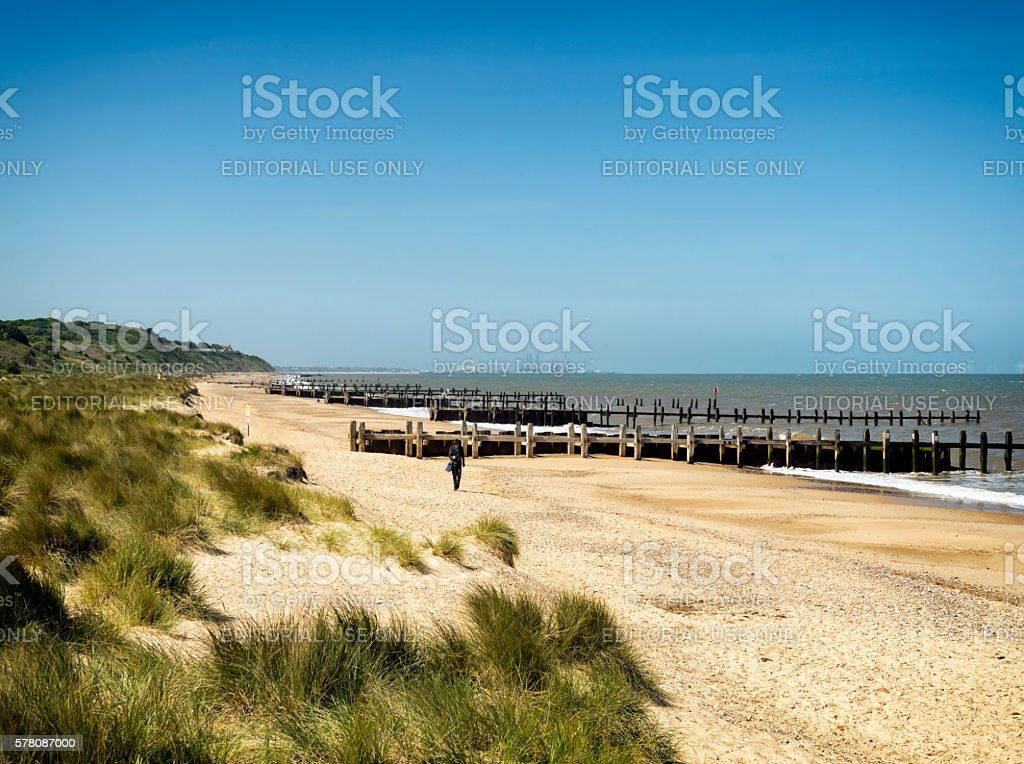 Woman walking along Gunton Denes beach, Suffolk stock photo