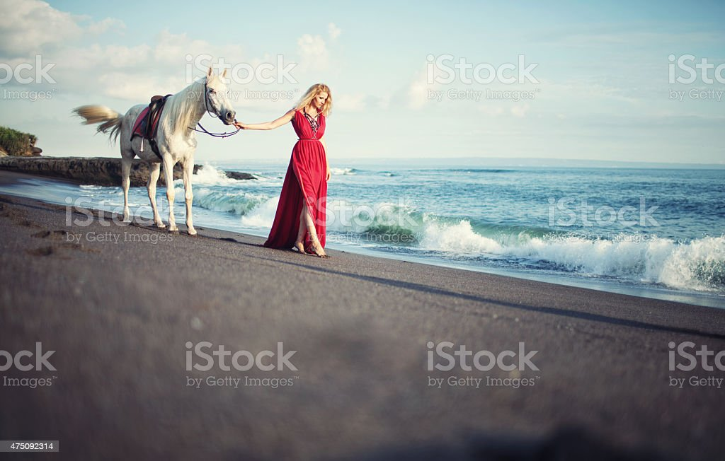 Woman walking along the beach with a horse stock photo