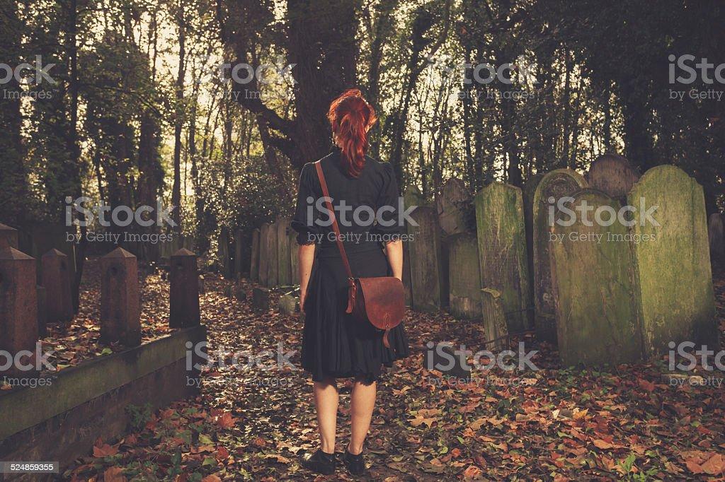 Woman walking amongst tombstones stock photo