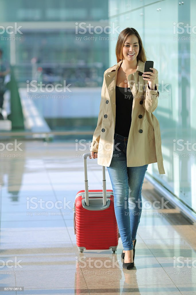 Woman walking and using a smart phone in an airport stock photo
