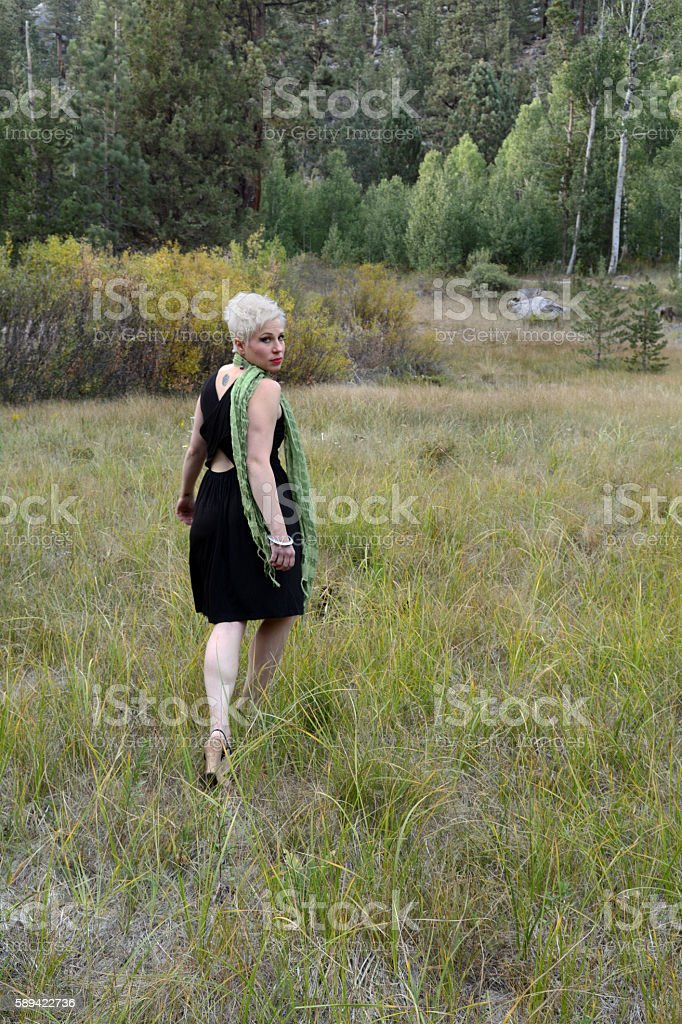 Woman Walking Away From Camera and Looking Back royalty-free stock photo