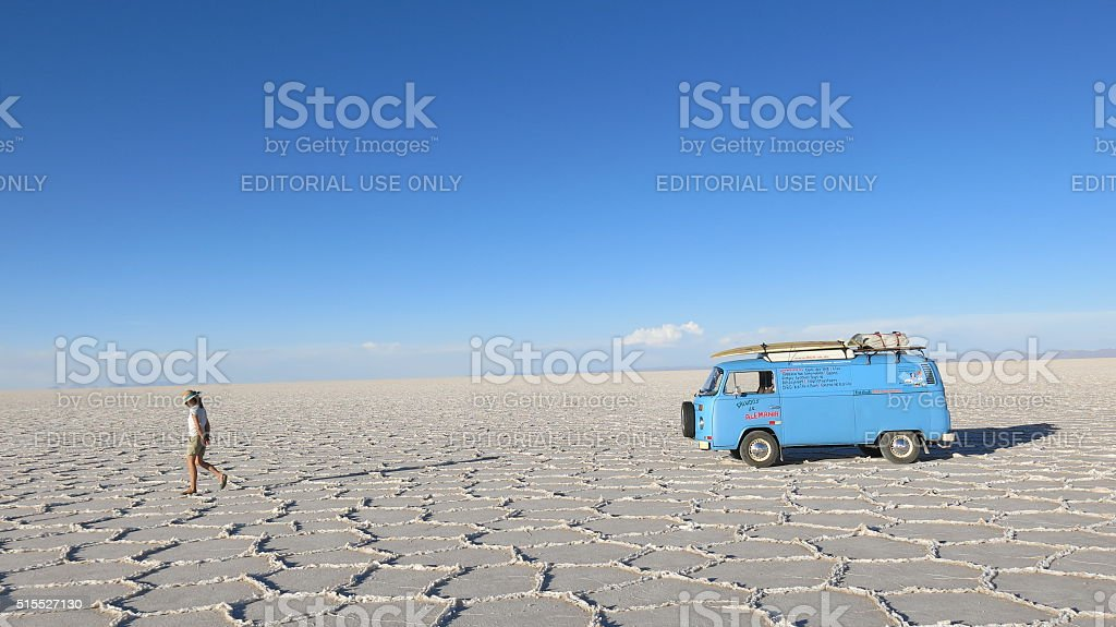 Woman walking away from VW bus on Salar de Uyuni stock photo